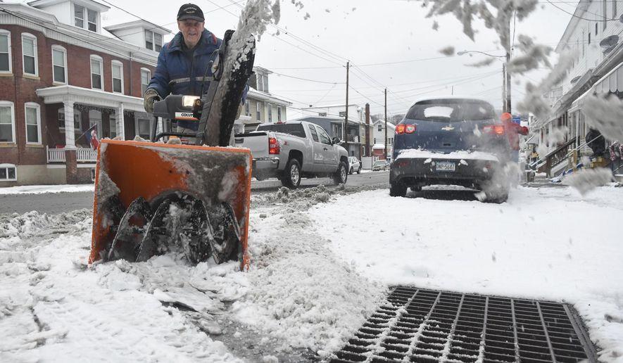 Lee Miller, Port Carbon, Pa., cuts through the snow on Coal Street in Port Carbon, Pa., on Thursday, Dec. 29, 2016. (Jacqueline Dormer/Republican-Herald via AP)