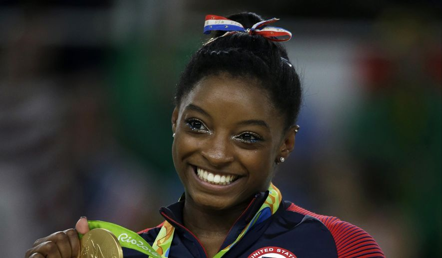 In this Aug. 16, 2016, file photo, United States' Simone Biles displays her gold medal for the floor routine during the artistic gymnastics women's apparatus final at the 2016 Summer Olympics in Rio de Janeiro, Brazil. (AP Photo/Rebecca Blackwell, File)