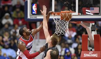 Washington Wizards guard John Wall, left, dunks over Brooklyn Nets center Justin Hamilton, right, during the second half of an NBA basketball game, Friday, Dec. 30, 2016, in Washington. The Wizards won 118-95. (AP Photo/Nick Wass)