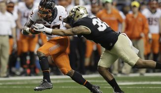 Oklahoma State running back Chris Carson, left, is hit by Colorado linebacker Rick Gamboa as he runs for a first down during the second half of the Alamo Bowl NCAA college football game, Thursday, Dec. 29, 2016, in San Antonio. (AP Photo/Eric Gay)