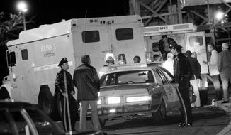 FILE - In this Oct. 21, 1981, file photo, police are at the scene of a Brinks armored truck robbery at the Nanuet Mall in Nanuet, N.Y., where multiple Nyack police officers and a Brinks guard were killed earlier during the robbery. Judith Clark is a former Weather Underground member who has served 35 years of a 75-year-to-life sentence for her role in the robbery, will be eligible for parole in 2017 following a commutation from New York Gov. Andrew Cuomo on Friday, Dec. 30, 2016. (AP Photo/File)
