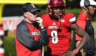 FILE - In this Oct. 22, 2016, file photo, Louisville head coach Bobby Petrino talks with Lamar Jackson (8) during a time out in their NCAA college football game against North Carolina State in Louisville, Ky.  At different points of the season, LSU and Louisville were contenders for the four-team College Football Playoffs. The Tigers entered the season fifth in the Top 25 and late into the regular season the Cardinals were No.5 in the College Football Playoff poll. But losses knocked both out of the CFP mix and the landed in Saturday's Citrus Bowl. (AP Photo/Timothy D. Easley, File)