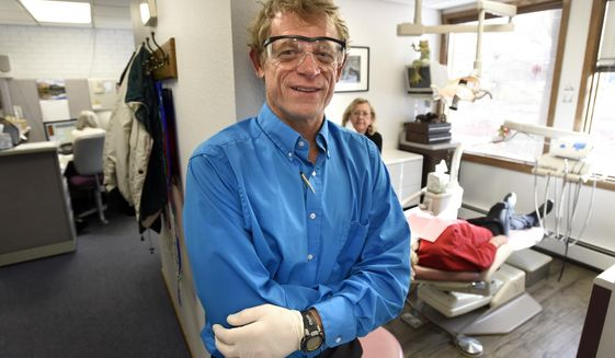 In this Tuesday, Dec. 20, 2016 photo, Thomas Bogan, DDS, poses at his dental office  in Boulder, Colo. Bogan recently earned a spot to compete in the Kona Ironman race. (Jeremy Papasso /Daily Camera via AP)