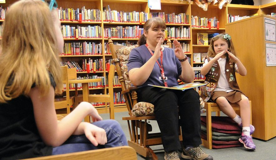 "ADVANCE FOR USE SATURDAY, DEC. 31, 2016, AT 9:01 A.M. EST AND THEREAFTER  In this Wednesday, Dec. 28, 2016 photo, Elizabeth Francke, from left, 8, watches as Katrina M. Hosking, children's librarian at South Berkeley Community Library at Musselman High School, and her daughter Lillian Hosking, 7, use sign language while reading ""Are You My Mommy?"" during storytime at the library in Inwood, WVa. Lillian's signing skills are also helping her earn a ""speaking in sign"" merit badge from the Girl Scouts of the Chesapeake bay. Hosking herself puts her sign language skills to work each Tuesday and Wednesday, overseeing ""Sign With Me Storytime,"" a half-hour kids program that combines children's book story telling with sign language. (Ron Agnir/The Journal via AP)"