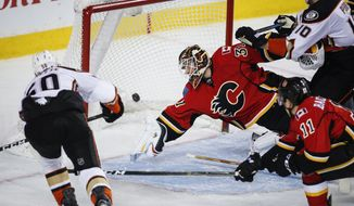 Anaheim Ducks' Antoine Vermette, left, scores against Calgary Flames goalie Chad Johnson during second-period NHL hockey action in Calgary, Alberta, Thursday, Dec. 29, 2016. (Jeff McIntosh/The Canadian Press via AP)