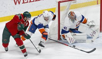Minnesota Wild's Zach Parise, left, shoots as New York Islanders' Thomas Hickey, center, and goalie Jaroslav Halak of Slovakia defend the net during the first period of an NHL hockey game Thursday, Dec. 29, 2016, in St. Paul, Minn. (AP Photo/Jim Mone)