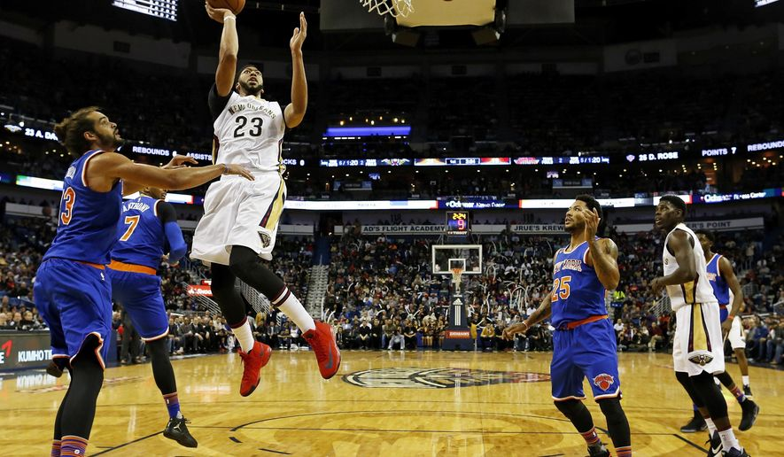 New Orleans Pelicans forward Anthony Davis (23) makes a layup over New York Knicks center Joakim Noah, left, and New York Knicks guard Derrick Rose, right, in the first half of an NBA basketball game in New Orleans, Friday, Dec. 30, 2016. (AP Photo/Max Becherer)