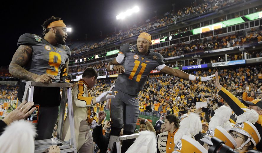 """Tennessee quarterback Joshua Dobbs (11) and defensive end Derek Barnett (9) lead the marching band in the playing of """"Rocky Top"""" after Tennessee defeated Nebraska in the Music City Bowl NCAA college football game Friday, Dec. 30, 2016, in Nashville, Tenn. (AP Photo/Mark Humphrey)"""