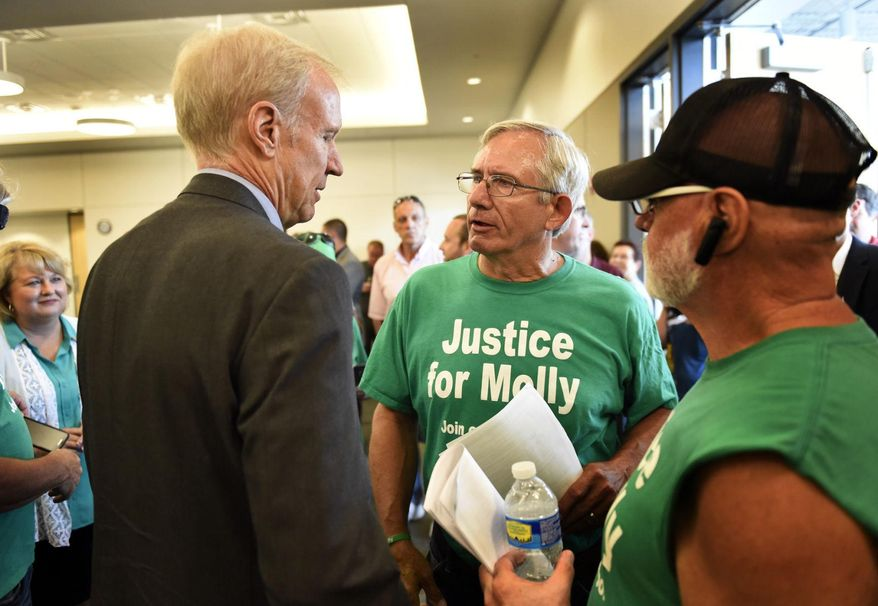 """FILE - In this July 19, 2016 file photo, Gov. Bruce Rauner, left, speaks with Larry Young, center, father of Molly Young, after Rauner signed the two bills collectively known as """"Molly's Law"""" in Carbondale, Ill. The law that takes effect Jan. 1, 2017 extends the statute of limitations, from two years to five, on bringing wrongful death lawsuits and increase fines for public bodies that don't comply with court orders to release information. """"Molly's Law,"""" is named after Molly Young, a Carbondale woman fatally shot in 2012 and found in her ex-boyfriend's apartment. (Byron Hetzler  /The Southern Illinoisan via AP, File)"""