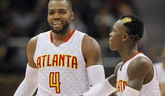 Atlanta Hawks forward Paul Millsap (4) and guard Dennis Schroder (17) reacts after Milsap scored late in the second half of an NBA basketball game between the Detroit Pistons and Atlanta Hawks on Friday, Dec. 30, 2016, in Atlanta. The Hawks won the game 105-98. (AP Photo/Todd Kirkland)