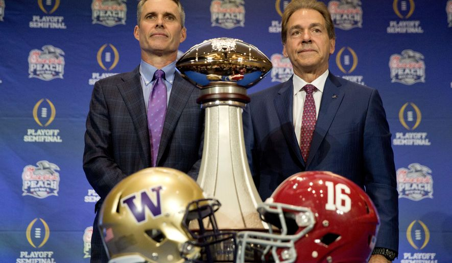 Alabama head coach Nick Saban, right, and Washington head coach Chris Petersen pose for a photo with the trophy during an NCAA college football press conference for the Peach Bowl, Friday, Dec. 30, 2016 in Atlanta. Washington plays Alabama on Saturday. (AP Photo/David Goldman)