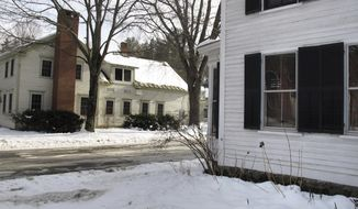 In this photo taken Dec. 20, 2016, a home with shutters, at right, is next to a home without shutters in Woodstock, Vt. The village of Woodstock is cracking down on homeowners who are refusing to keep shutters on their homes. Officials say the loss of shutters would hurt the village's historic character. (AP Photo/Wilson Ring)