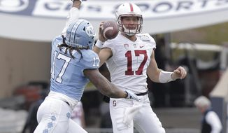 Stanford quarterback Ryan Burns (17) looks for a receiver while covered closely by North Carolina defensive end Dajaun Drennon in the second quarter duofing the Sun Bowl NCAA college football game Friday, Dec. 30, 2016, in El Paso, Texas. (AP Photo/Mark Lambie)