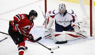 New Jersey Devils center Adam Henrique (14) skates in on Washington Capitals goalie Philipp Grubauer (31), of Germany, during the third period of an NHL hockey game, Saturday, Dec. 31, 2016, in Newark, N.J. (AP Photo/Julio Cortez)