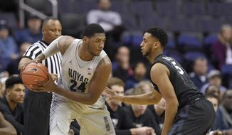 Georgetown forward Marcus Derrickson (24) handles the ball against Xavier guard Trevon Bluiett (5) during the first half of an NCAA college basketball game, Saturday, Dec. 31, 2016, in Washington. (AP Photo/Nick Wass) **FILE**