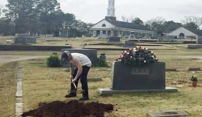 """ADVANCE FOR WEEKEND EDITIONS - FILE - In this Saturday, Feb. 20, 2016, file photo, a man rakes soil over a grave in the Lee family cemetery plot, in Monroeville, Ala. Harper Lee, the author of """"To Kill a Mockingbird,"""" died Friday, Feb. 19. Literary icon Harper Lee died in February at age of 89. Lee had stunned the world a year earlier when her publisher announced that a second novel """"Go Set a Watchman"""" would be published. Lee was buried in a quiet service in Monroeville with only a few select friends and family present, a reflection of how the famously private author had lived her life. (AP Photo/Kim Chandler, File)"""