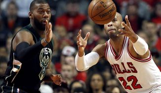 Chicago Bulls forward Taj Gibson, right, reaches for the ball next to Milwaukee Bucks' Greg Monroe during the first half of an NBA basketball game Saturday, Dec. 31, 2016, in Chicago. (AP Photo/Nam Y. Huh)