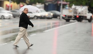 A man looks at opposing traffic as he crosses N. Placentia Ave. as a light, warm rain falls on Friday morning, Dec. 30, 2016, in Anaheim. California's wet December is drawing to a close with even more rain and snow in a welcome respite amid years of drought. A warm low-pressure storm system brought showers to Southern California starting early Friday and slowly moved east through the day as a cold weather system dropped down toward the state from the north. (Ken Steinhardt/The Orange County Register via AP)