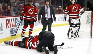 A trainer looks at New Jersey Devils defenseman John Moore (2) after he suffered an injury during the first period of an NHL hockey game against the Washington Capitals, Saturday, Dec. 31, 2016, in Newark, N.J. Also seen are Devils' Andy Greene (6) and Keith Kinkaid (1). Moore was taken off the ice on a stretcher. (AP Photo/Julio Cortez)