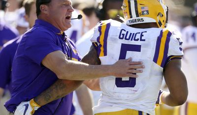 LSU head coach Ed Orgeron celebrates with running back Derrius Guice (5) after a touchdown against Louisville during the first half of the Citrus Bowl NCAA football game, Saturday, Dec. 31, 2016, in Orlando, Fla. (Stephen M. Dowell/Orlando Sentinel via AP)