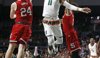 Miami guard Bruce Brown (11) drives to the basket between North Carolina State's Maverick Rowan, left, and another defender during an NCAA college basketball game Saturday, Dec. 31, 2016, in Coral Gables, Fla. (Al Diaz/Miami Herald via AP)