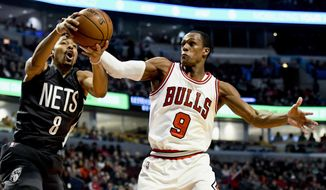 Brooklyn Nets guard Spencer Dinwiddie (8) and Chicago Bulls guard Rajon Rondo (9) fight for a rebound during the first half of an NBA basketball game Wednesday, Dec. 28, 2016, in Chicago. (AP Photo/Matt Marton)