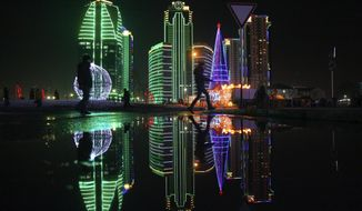FILE- In this Wednesday, Dec. 28, file photo, a Christmas tree and skyscrapers illuminated for the New Year celebrations are seen in downtown Grozny, the capital of Chechnya, Russia. (AP Photo/Musa Sadulayev, File)