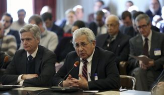 FILE - In this Dec. 15, 2016 file photo, Stephen W. Parker, left, co-owner and co-publisher of New Jersey Hills Media Group, listens as Richard Vezza, publisher of the Star-Ledger newspaper, addresses members of the New Jersey Assembly Appropriations Committee, as the committee considers among others, legislation to scrap a requirement that legal notices be published in newspapers, after a Senate budget committee greenlighted the legislation earlier in the day, in Trenton. As classified advertising, once the lifeblood of newspapers, has dried up, one constant has remained: A thick daily listing of government public notices. But legislative fights in New Jersey and elsewhere have put that tradition at risk. (AP Photo/Mel Evans, File)