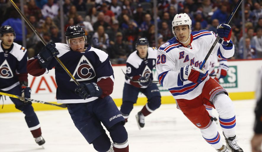 Colorado Avalanche defenseman Tyson Barrie, left, pursues the puck to the boards with New York Rangers left wing Chris Kreider in the second period of an NHL hockey game Saturday, Dec. 31, 2016, in Denver. (AP Photo/David Zalubowski)