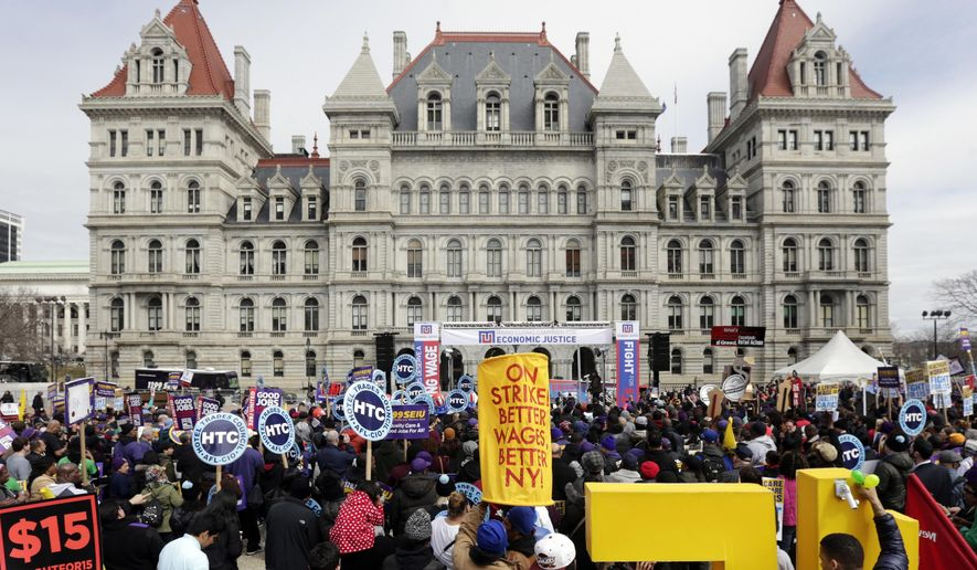 FILE - In this March 15, 2016 file photo, the state Capitol provides a backdrop as supporters of a $15 minimum wage rally at the Empire State Plaza in Albany, N.Y. The year 2016 saw New York raise the minimum wage and extend paid family leave while state officials confronted yet another corruption scandal. (AP Photo/Mike Groll, File)
