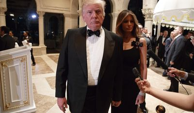 Melania Trump, right, looks on as her husband President-elect Donald Trump talks to reporters during a New Year's Eve party at Mar-a-Lago, Saturday, Dec. 31, 2016, in Palm Beach, Fla. (AP Photo/Evan Vucci)