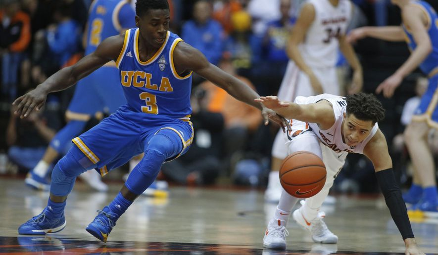 UCLA's Aaron Holiday, left, and Oregon State's JaQuori McLaughlin chase after a loose ball during the first half of an NCAA college basketball game in Corvallis, Ore., Friday, Dec. 30, 2016. (AP Photo/Timothy J. Gonzalez)