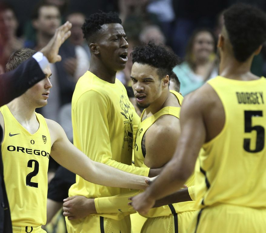 Oregon's Casey Benson, left, Kavell Bigby-Williams, Dillon Brooks, and Tyler Dorsey celebrate after taking the lead against Southern California during the first half of an NCAA college basketball game Friday, Dec. 30, 2016, in Eugene, Ore. (AP Photo/Chris Pietsch)