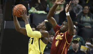 Oregon's Dylan Ennis, left, goes up for a layup against Southern California's Chimezie Metu during the second half of an NCAA college basketball game Friday, Dec. 30, 2016, in Eugene, Ore. (AP Photo/Chris Pietsch)