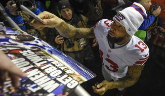 New York Giants wide receiver Odell Beckham (13) hands the pen back after autographing a poster after an NFL football game against the Washington Redskins in Landover, Md., Sunday, Jan. 1, 2017. The New York Giants defeated the Washington Redskins 19-10. (AP Photo/Nick Wass)