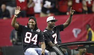Former Atlanta Falcons players Roddy White, left, and Michael Vick are seen during halftime of an NFL football game between the Atlanta Falcons and the New Orleans Saints, Sunday, Jan. 1, 2017, in Atlanta. (AP Photo/John Bazemore)