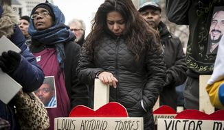 Veronica Aguilera, 31, carries the cross for her husband, Louis Antonio Torres, who was shot to death in November, during a quiet march along Michigan Avenue, Saturday, Dec. 31, 2016, in Chicago. Hundreds of people carried crosses for each person slain in Chicago in 2016 during the march. (Ashlee Rezin/Chicago Sun-Times via AP)