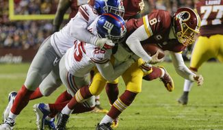 New York Giants outside linebacker Devon Kennard (59) and defensive back Leon Hall (25) sack Washington Redskins quarterback Kirk Cousins (8) during the second half of an NFL football game in Landover, Md., Sunday, Jan. 1, 2017. (AP Photo/Mark Tenally)