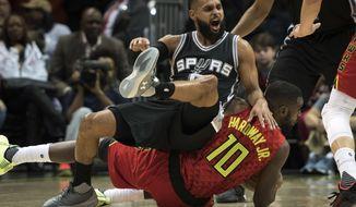 San Antonio Spurs guard Patty Mills, top, of Australia, falls on Atlanta Hawks guard Tim Hardaway Jr. while going for the ball during the first half of an NBA basketball game, Sunday, Jan. 1, 2017, in Atlanta. (AP Photo/John Amis)