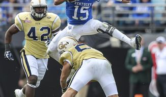 Kentucky quarterback Stephen Johnson (15) leaps over Georgia Tech linebacker Brant Mitchell during the second half of the TaxSlayer Bowl NCAA college football game at EverBank Field in Jacksonville, Fla., Saturday, Dec. 31, 2016. Georgia Tech won 33-18. (Gary Lloyd McCullough/The Florida Times-Union via AP)
