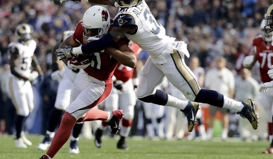 Los Angeles Rams free safety Maurice Alexander, right, tackles Arizona Cardinals wide receiver Larry Fitzgerald during the first half of an NFL football game Sunday, Jan. 1, 2017, in Los Angeles. (AP Photo/Jae C. Hong)