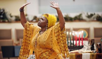 In this Tuesday, Dec. 27, 2016, Dr. Nubian Sun, of Bowling Green, performs a dance for the principle of Kuumba or creativity during the 16th annual Community Kwanzaa celebration at First Christian Church, in Bowling Green, Ky. (Miranda Pederson/Daily News via AP)