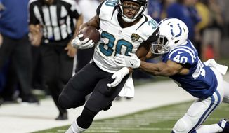 Jacksonville Jaguars running back Corey Grant (30) runs out of a tackle of Indianapolis Colts cornerback Christopher Milton (40) during the first half of an NFL football game in Indianapolis, Sunday, Jan. 1, 2017. (AP Photo/Darron Cummings)