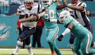 New England Patriots quarterback Tom Brady (12) runs the ball ahead of Miami Dolphins defensive tackle Earl Mitchell (90) and defensive end Andre Branch (50), during the first half of an NFL football game, Sunday, Jan. 1, 2017, in Miami Gardens, Fla. (AP Photo/Lynne Sladky)