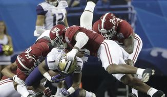 Washington wide receiver John Ross (1) is tackled by Alabama defensive lineman Dalvin Tomlinson (54) and Alabama linebacker Reuben Foster (10) during the first half of the Peach Bowl NCAA college football playoff game, Saturday, Dec. 31, 2016, in Atlanta. (AP Photo/David Goldman)