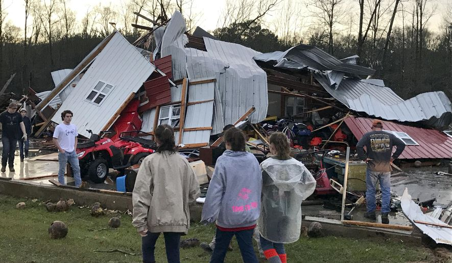 People examine a barn owned by the Miller family that was destroyed during a storm south of Mount Olive, Miss., Monday, Jan. 2, 2017. Forecasters say damaging winds, hail and flash flooding will be possible on Monday as a storm system moves across the South. (Ryan Moore/WDAM-TV via AP)