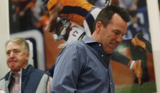 Gary Kubiak, front, heads to the podium to step down as head coach of the Denver Broncos because of health concerns Monday, Jan. 2, 2017, at team headquarters in Englewood, Colo. Joe Ellis, team chief executive officer and president, left, looks on. (AP Photo/David Zalubowski)