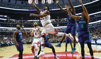 Chicago Bulls forward Jimmy Butler (21) goes to the basket against Charlotte Hornets forward Marvin Williams (2) and guard Jeremy Lamb (3) during the first half of an NBA basketball game, Monday, Jan. 2, 2017, in Chicago. (AP Photo/Kamil Krzaczynski)