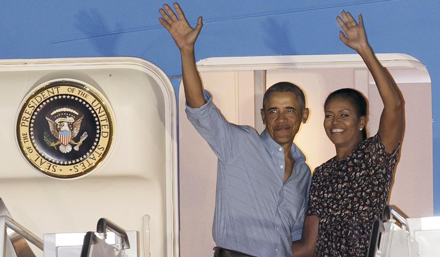 U.S. President Barack Obama and first lady Michelle Obama wave at people from Air Force One as they leave Joint Base Pearl Harbor-Hickam, adjacent to Honolulu, Hawaii, en route to Washington, Sunday, Jan. 1, 2017, after their annual family vacation on the island of Oahu. (AP Photo/Marco Garcia)