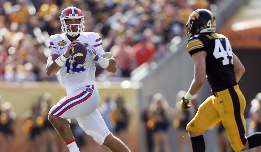 Florida quarterback Austin Appleby (12) looks to throw the ball on the run from Iowa linebacker Ben Niemann (44) in the first half during the Outback Bowl NCAA college football game in Tampa, Fla., Monday, Jan. 2, 2017. (Andres Leiva/Tampa Bay Times via AP)